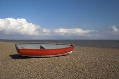 Rotes Boot auf Dunwich-Strand, Suffolk, England stockfotografie