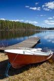 Rotes Boot auf Frühlingsseeküste Stockfoto