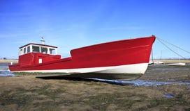 Rotes Boot bei Ebbe im Lege Schutzkappen-Frettchen Stockfoto