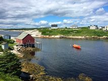 Rotes Boot, Häuser, grünes Gras, Sommer in Peggy Bucht, Kanada Stockfotos