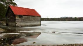 Rotes Bootshaus auf einem gefrorenen See Stockbild