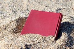 Rotes Buch auf dem Sand auf einem undeutlichen Hintergrund, umfasst mit dem Sand, begraben im Sand Stockbilder