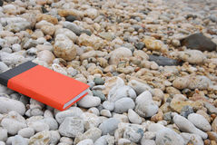 Rotes Buch auf Kiesel Stockfotos