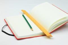 Rotes Buch, Bleistift und Machthaber Lizenzfreie Stockfotografie