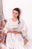 Rotes Buch der Frau in einem Bett Lizenzfreie Stockfotografie
