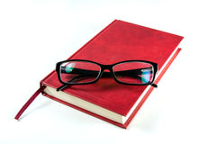 Rotes Buch und Lesebrille Stockfoto