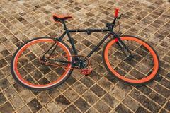 Rotes bycicle ist auf dem quadratischen Boden Stockbild