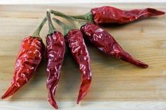 Rotes chillie auf hölzernem hackendem Vorstand des Wacholderbusches Stockbilder