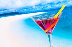 Rotes Cocktail auf Unschärfestrand mit Raum für Text Stockfotos