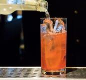 Rotes Cocktail, das in hohes Glas gegossen wird stockbilder