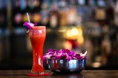 Rotes Cocktail mit Orchideenblume in der Bar Stockbilder