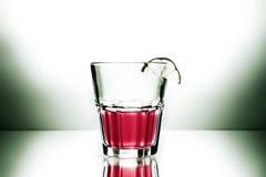 Rotes Cocktail mit Spritzen und Kalk Stockfoto