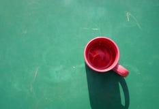 Rotes Cup auf Grün Stockbilder