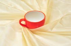 Rotes Cup am goldenen Gewebedrapierung Lizenzfreies Stockfoto