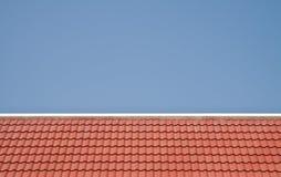 Rotes Dach auf Hintergrund des blauen Himmels Stockfotos