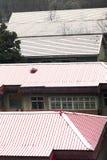 Rotes Dach bedeckt mit Schnee Stockbilder