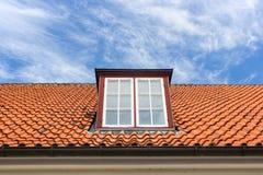 Rotes Dach mit einem Mansardenfenster Lizenzfreie Stockbilder