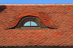 Rotes Dach mit romantischem Fenster. Stockfotografie