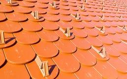 Rotes Dach mit Schneefängen Stockfotos