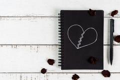 Rotes defektes Herz mit dem getrocknetem rosafarbenen Blumenblatt und Notizbuch Stockfoto