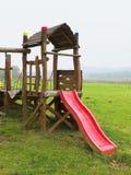Rotes Dia vom hölzernen Schleichenbau auf modernem Kinderspielplatz Lizenzfreies Stockfoto