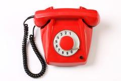 Rotes Drehtelefon auf weißem Hintergrund Stockfotos