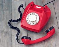 Rotes Drehtelefon weg vom Haken auf einer hölzernen Plattform Lizenzfreie Stockfotos