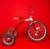 Rotes Dreirad der Weinlese auf einem hellen roten Hintergrund Stockfotografie