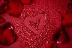 Rotes drowing Herz auf rotem Hintergrund mit den Blumenblättern der roten Rosen lizenzfreie stockfotos