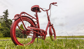 Rotes Fahrrad auf dem Straßenrand Lizenzfreie Stockbilder