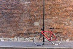 Rotes Fahrrad auf einem alten Backsteinmauerhintergrund Stockfoto