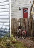 Rotes Fahrrad, das an einem alten Zaun auf einem Steinweg sich lehnt Lizenzfreies Stockbild