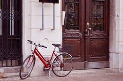 Rotes Fahrrad, das an einem Gebäude sich lehnt lizenzfreies stockfoto