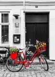 Rotes Fahrrad der Retro- Weinlese auf Kopfsteinstraße in der alten Stadt Lizenzfreies Stockfoto