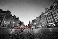 Rotes Fahrrad der Weinlese auf historischer alter Stadt des Kopfsteins im Regen Wroclaw, Polen Lizenzfreie Stockfotos
