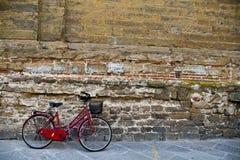 Rotes Fahrrad gegen Backsteinmauer Stockbild