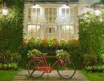 Rotes Fahrrad mit weißem Fenster und Gartenhintergrund Stockbild