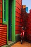 Rotes Fahrrad nahe bei einer roten Wand Stockfotografie