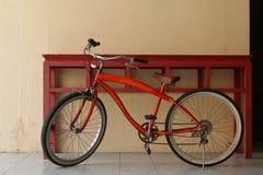 Rotes Fahrrad am roten Tisch Lizenzfreie Stockbilder
