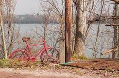 Rotes Fahrradparken nahe dem Fluss lizenzfreies stockfoto