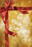 Rotes Farbband des Geschenks auf einem Goldhintergrund Stockfoto
