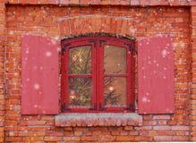 Rotes Fenster auf der Fassade des alten Backsteinhauses Weihnachtshintergrund, Winterfenster, Weihnachtsdekoration Lizenzfreies Stockbild