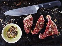 Rotes Fleisch und Gewürze über rustikalem Metallhintergrund Stockbilder