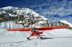 Rotes Flugzeug auf einem Gletscher Lizenzfreies Stockbild