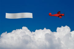 Rotes Flugzeug zieht unbelegte Fahne über weißen Wolken