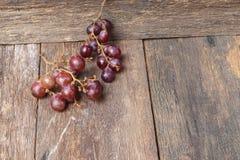 Rotes frisches der Traube auf Holztischhintergrund Stockfotos