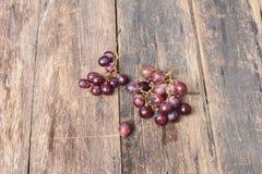 Rotes frisches der Traube auf Holztischhintergrund Stockfotografie