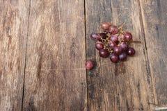 Rotes frisches der Traube auf Holztischhintergrund Stockbild