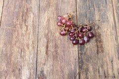 Rotes frisches der Traube auf Holztischhintergrund Lizenzfreie Stockfotos