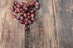 Rotes frisches der Traube auf Holztischhintergrund Lizenzfreies Stockfoto